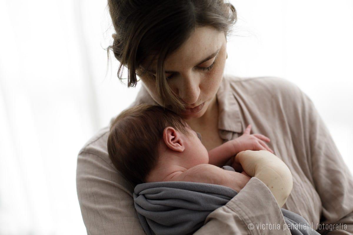 madre sostiene a su bebé arrullado en brazos