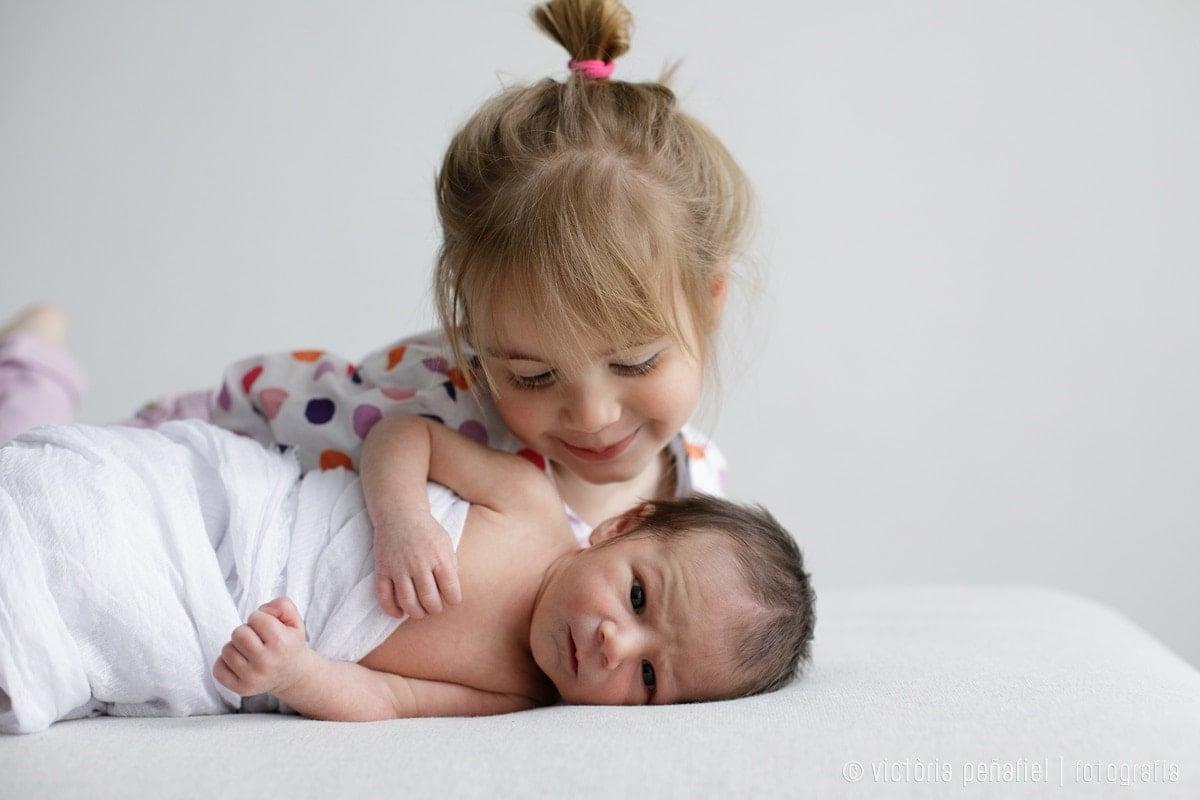 Hermana mayor mira sonriente a su bebé