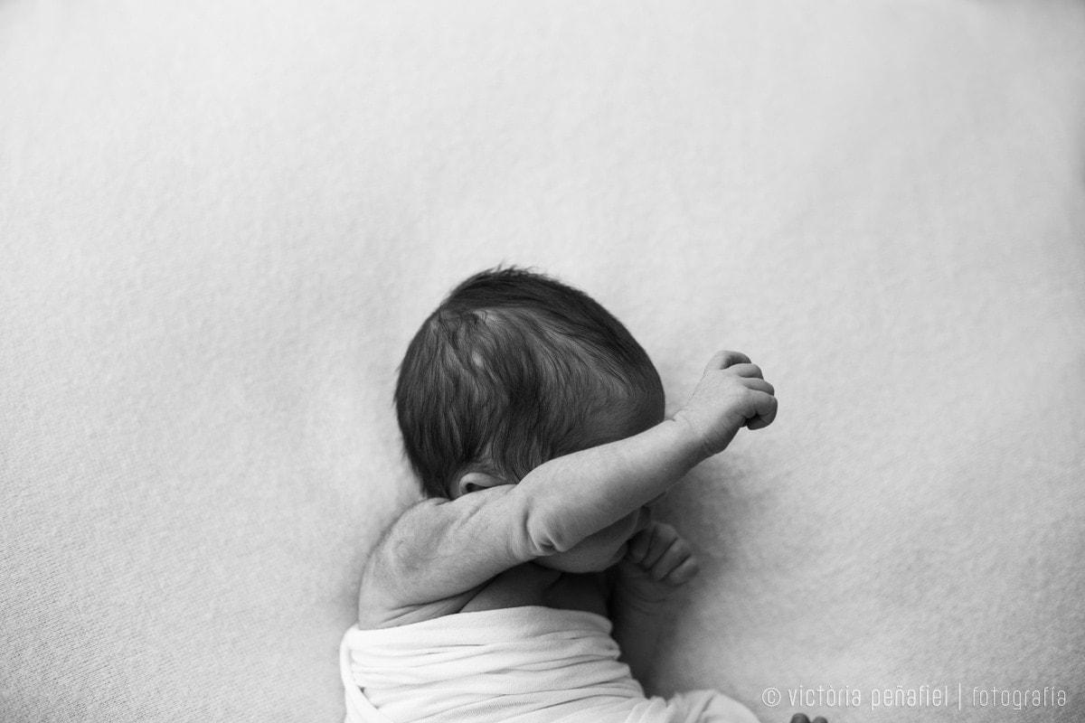 bebé recién nacido estirando el brazo medio dormido